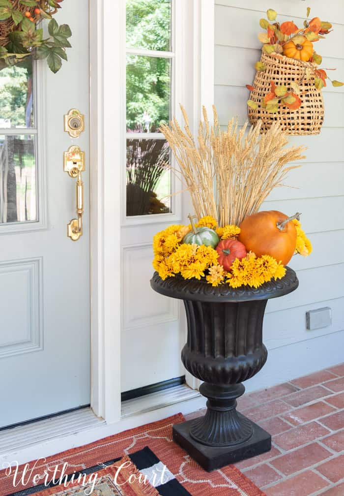 black urn filled with mums, pumpkins and wheat
