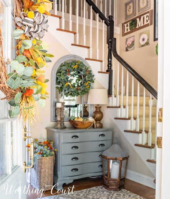 gray chest in foyer with L shaped stairway and fall decor