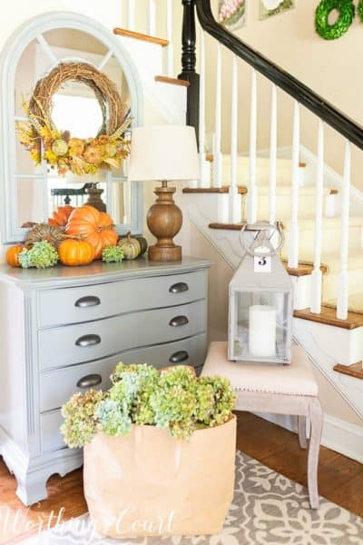 foyer with gray chest, arched mirror and fall decorations