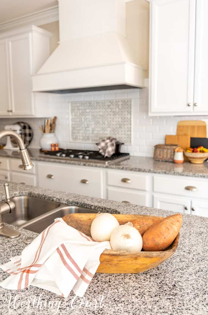 fall decor in kitchen with white cabinets and granite counters