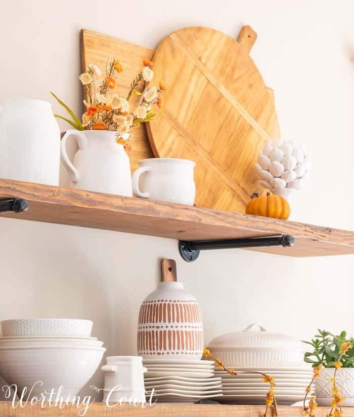 open shelves decorated for fall with white dishes