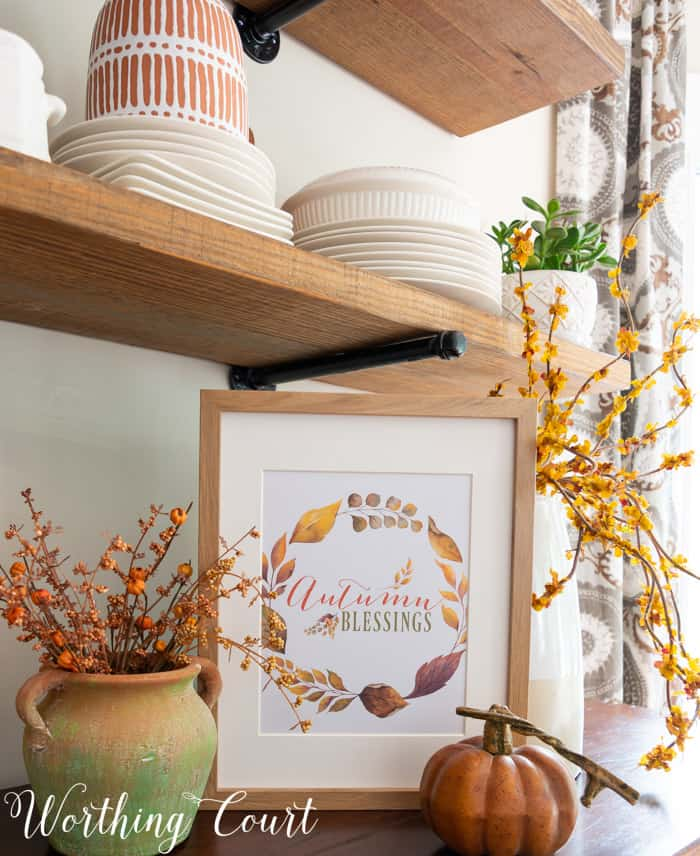 free printable with fall saying and colors displayed in a frame on a sideboard