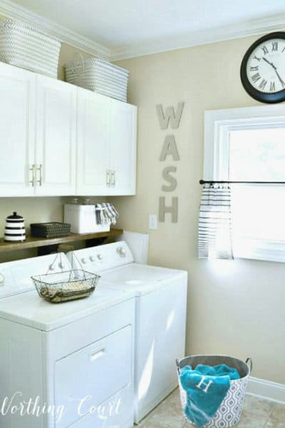 white washer and dryer with white cabinets above