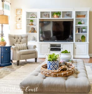 family room with white entertainment center with gray chair and gray coffee table