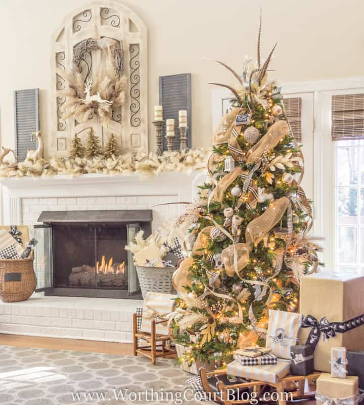 Christmas tree decorated with all neutral ornaments sitting beside fireplace