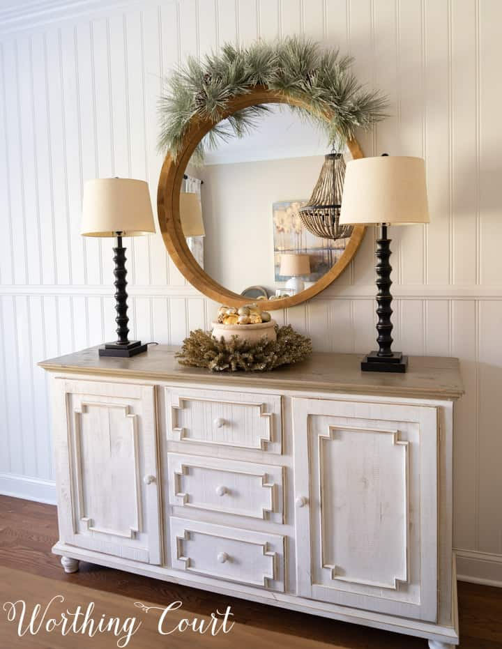 sideboard and round mirror decorated for Christmas