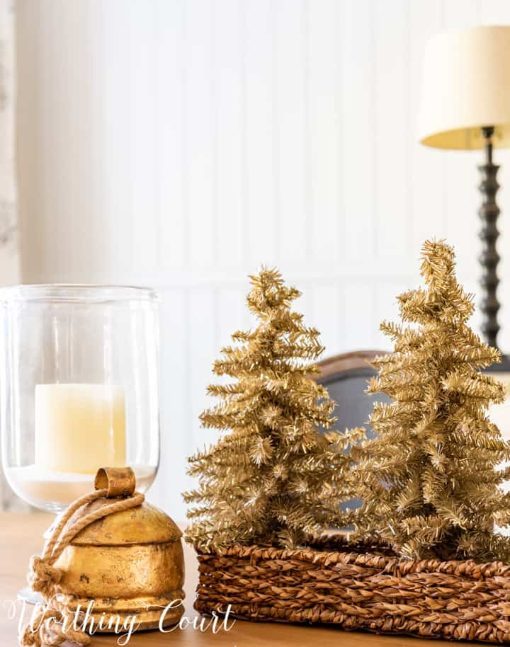 Christmas centerpiece with tinsel trees in a wicker basket, glass candle holders and a gold bell