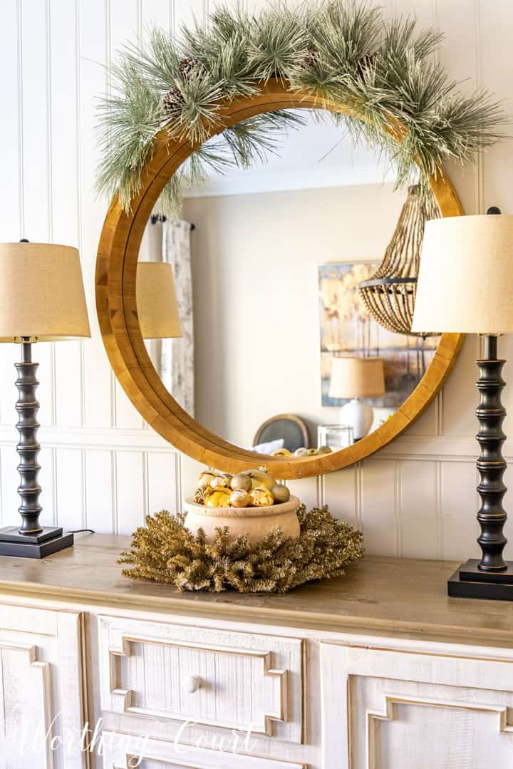 round mirror above sideboard with Christmas decorations