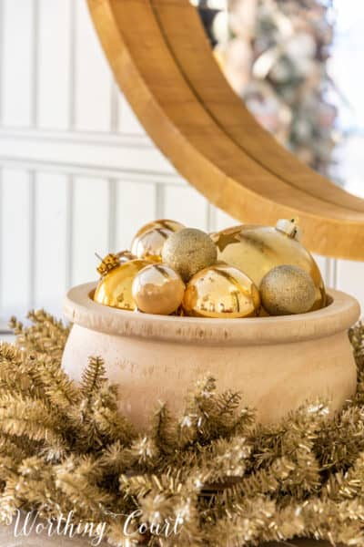 wood bowl filled with gold Christmas ornaments nestled in a tinsel wreath