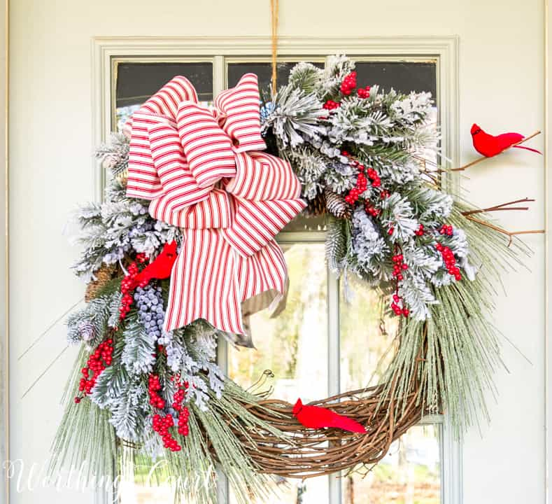 Christmas wreath with flocked pine branches, red cardinals and red and white striped ribbon