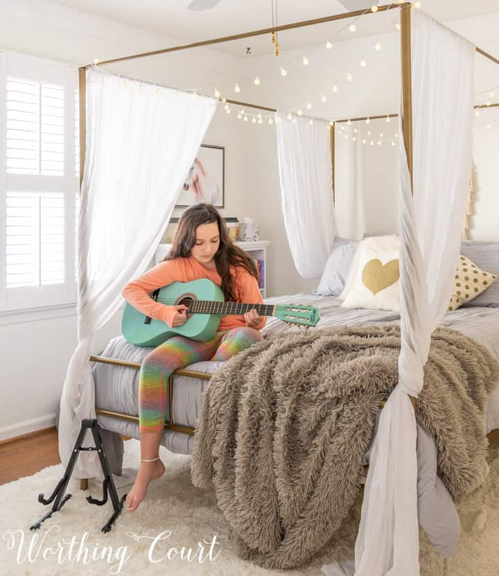 girl playing guitar sitting on the end of bed