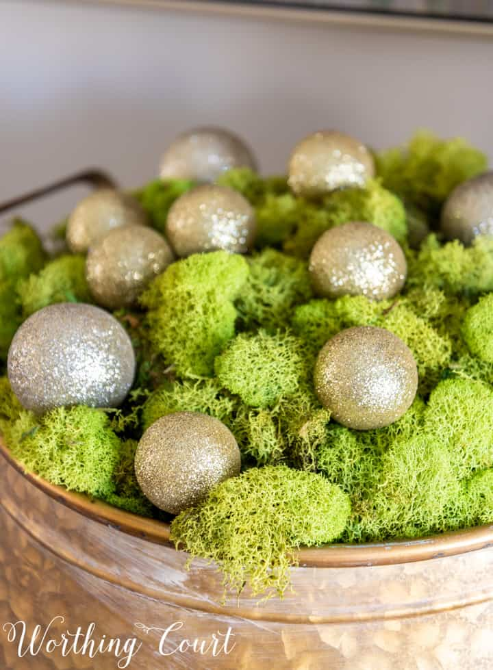 gold metal bowl filled with green moss and gold Christmas ornaments