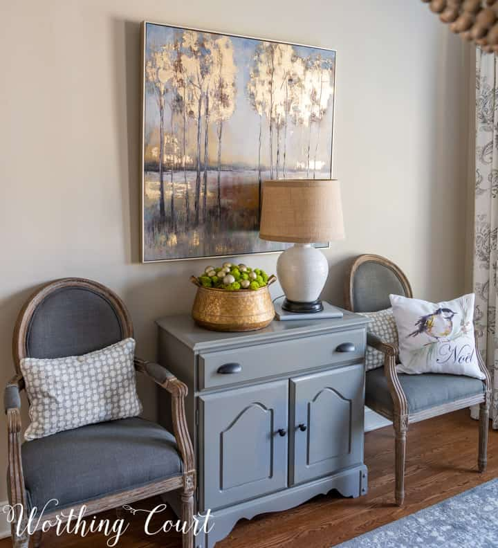 gray chest flanked by dining room chairs with artwork above