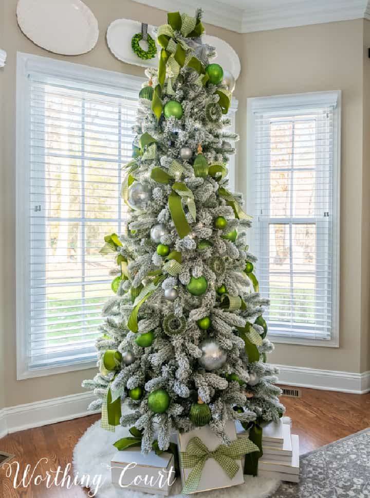 flocked Christmas tree with green and silver ornaments and ribbon