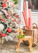 wooden horse beside flocked Christmas tree with red and white decorations