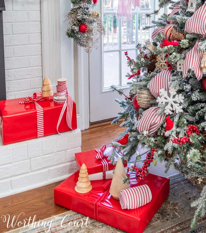 Christmas presents in red wrapping paper with red and white ribbon beside Christmas tree