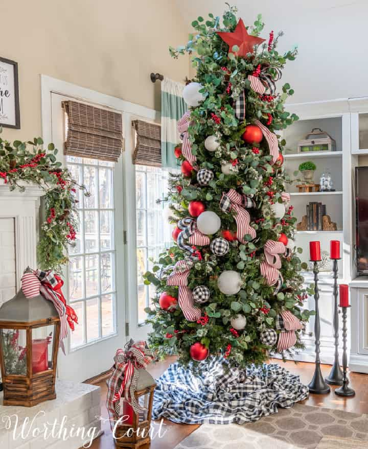 Christmas tree beside fireplace decorated with red, white and black