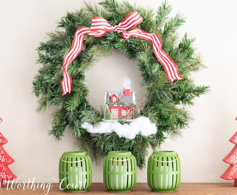 green Christmas wreath embellished with ribbon, fake snow and a tiny house