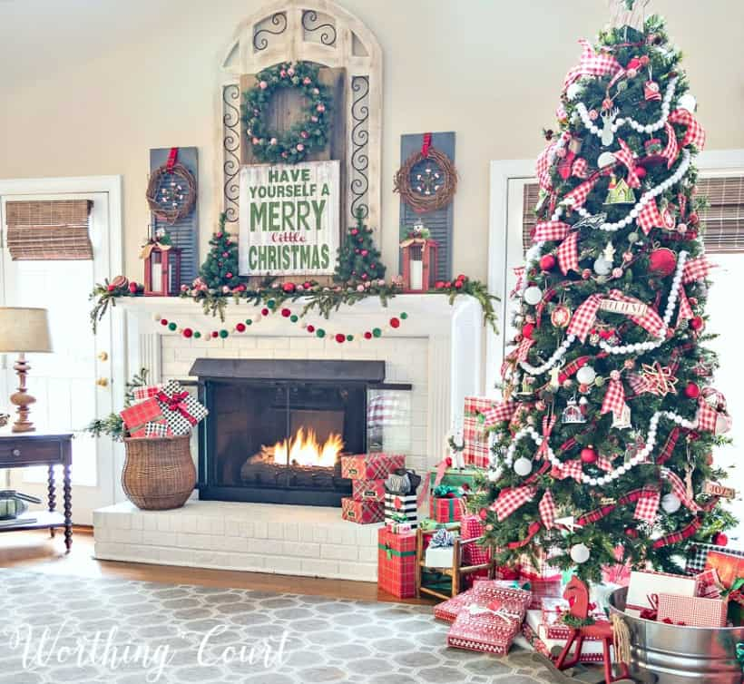Christmas tree decorated with red, black and white ornaments beside a fireplace