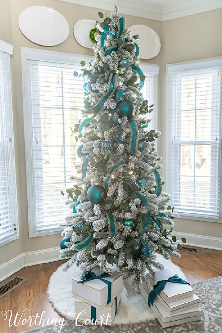 flocked Christmas tree with teal ornaments and ribbon