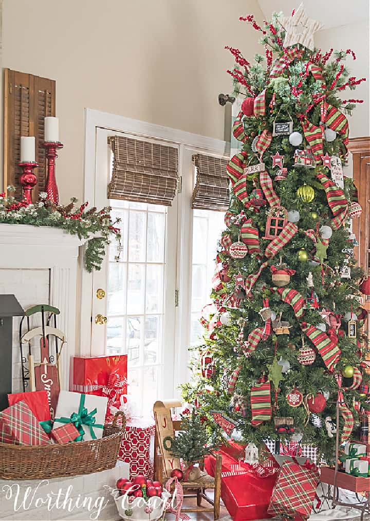 Christmas tree beside fireplace decorated with red and green ornaments and ribbon