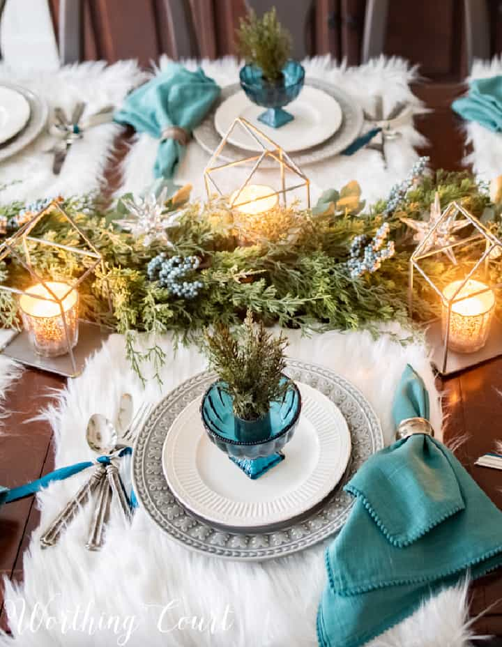 table setting with faux fur placemats and teal, gray and white dishware