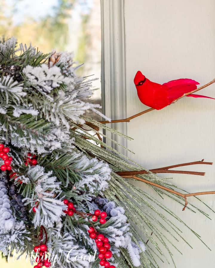 faux cardinal on a branch in a Christmas wreath