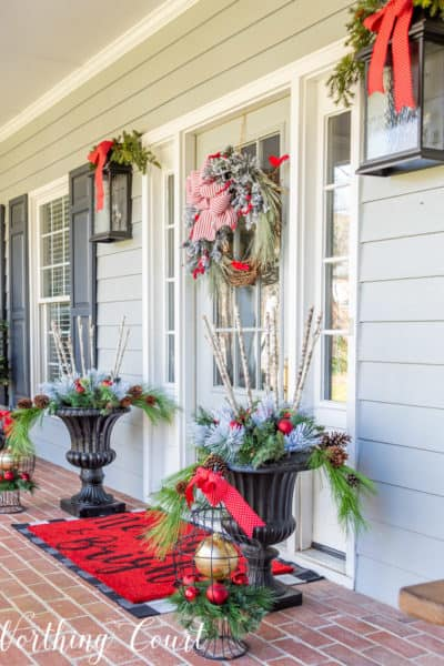 gray front door with Christmas wreath flanked by urns filled with Christmas decor