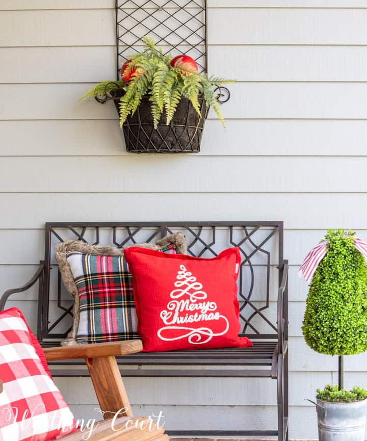 black outdoor bench with Christmas pillows