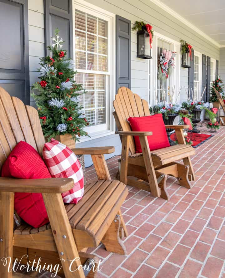 Adirondack chairs on porch with red and white pillows for Christmas