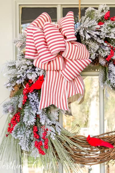 Christmas wreath with faux greenery, cardinals and red and white bow