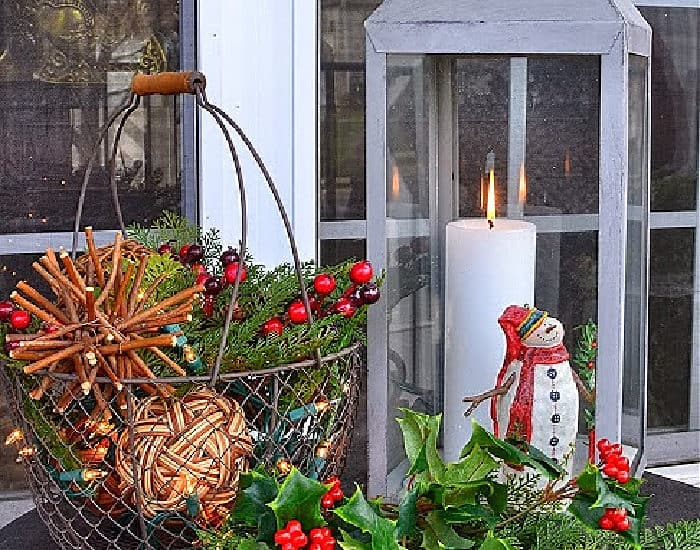 Christmas vignette with lantern, mini snowman, wire basket with orbs and faux greenery