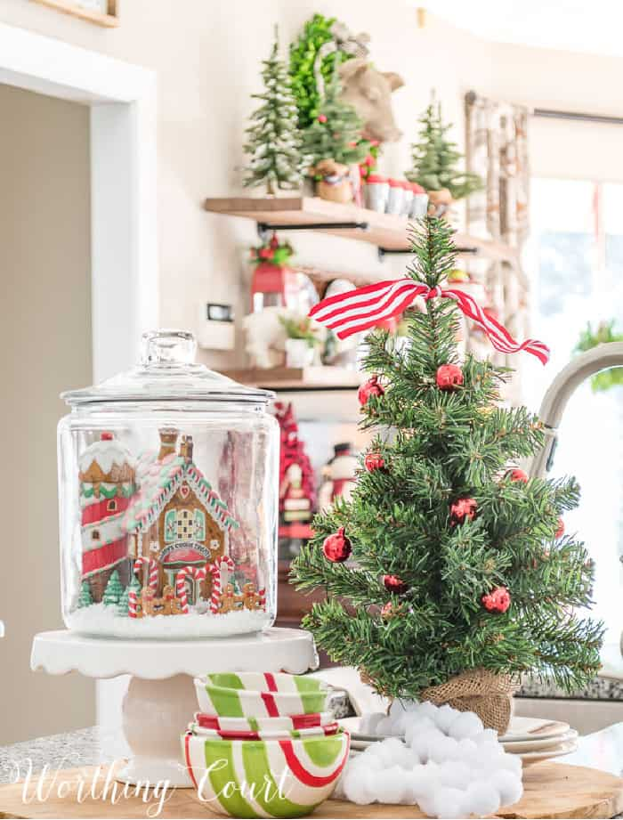 Christmas vignette with glass canister, mini tree, mini house on a cake pedestal