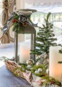 lantern with candle and mini Christmas tree in a wicker tray lined with a plaid scarf