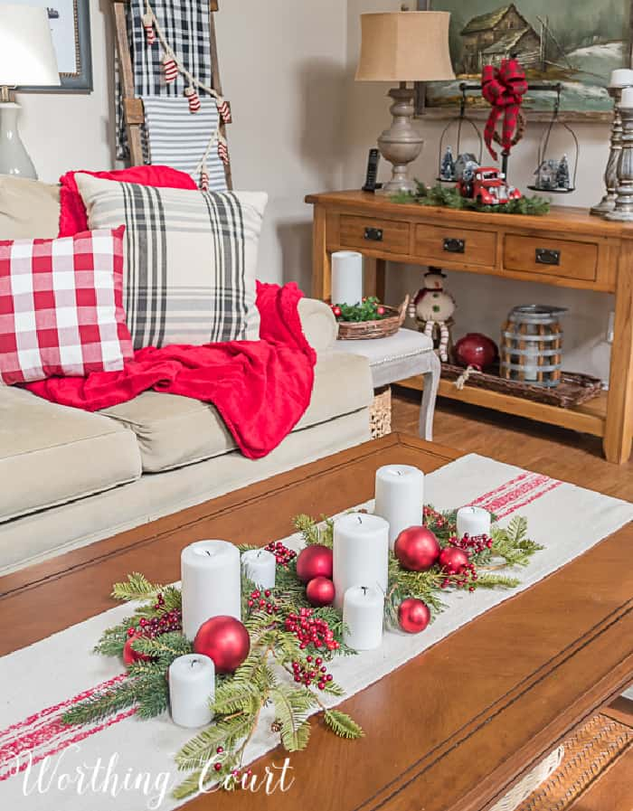 vignette with red and white runner on coffee table with white candles, red tree ornaments and faux greenery