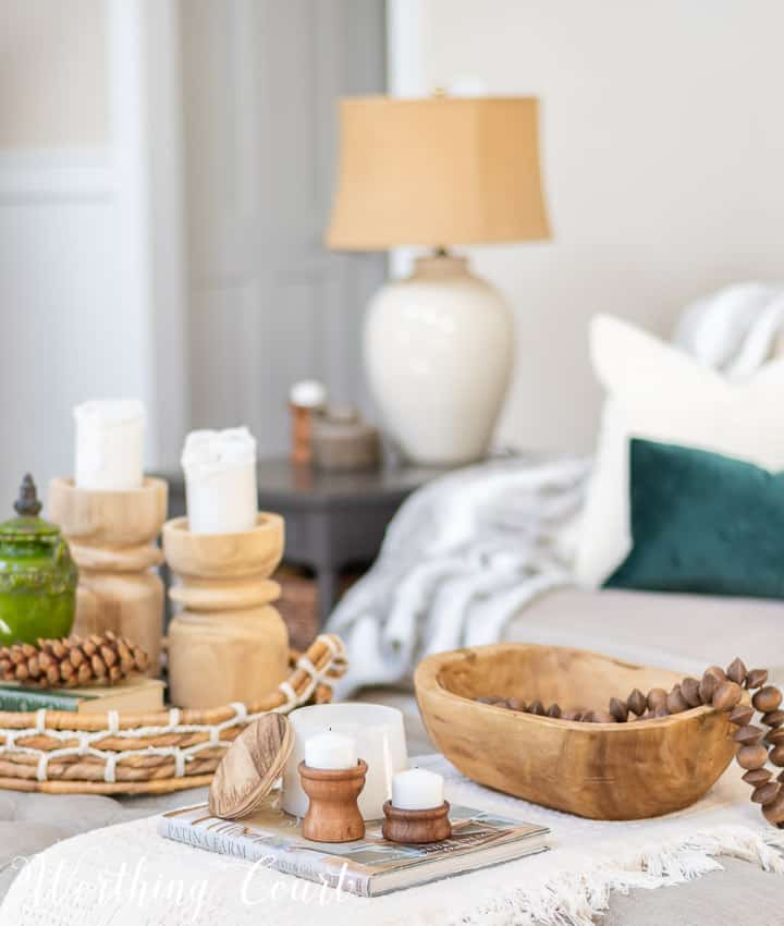 coffee table vignette with wood bowl, wood beads and wood candlesticks