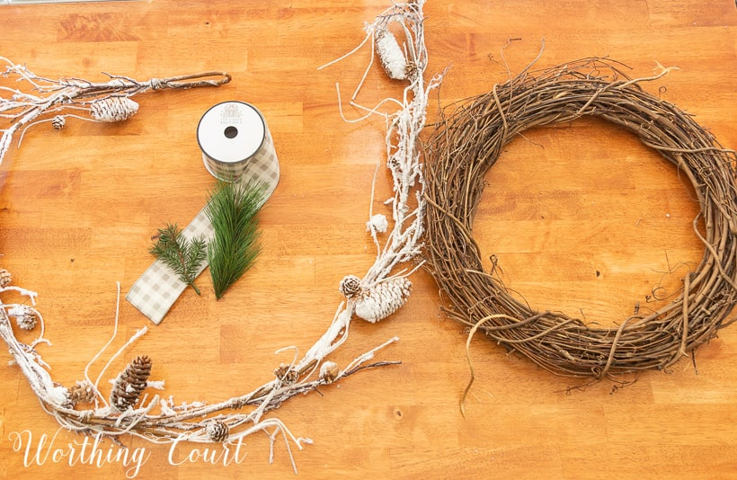 grapevine wreath, snowy garland, faux pine pieces and ribbon laying on a wood table
