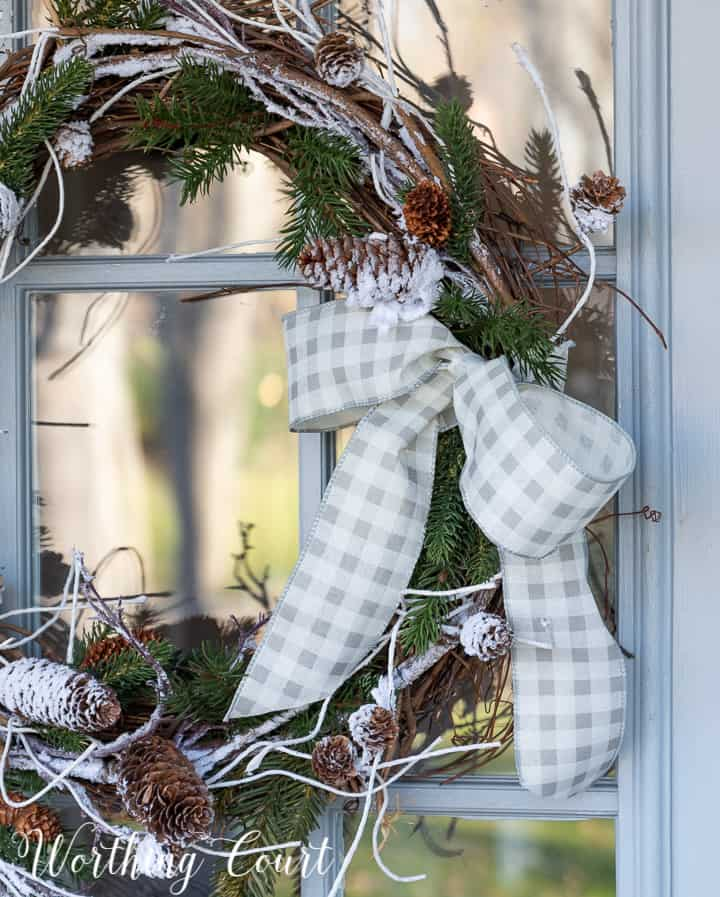 gray and white checked ribbon bow on a grapevine wreath
