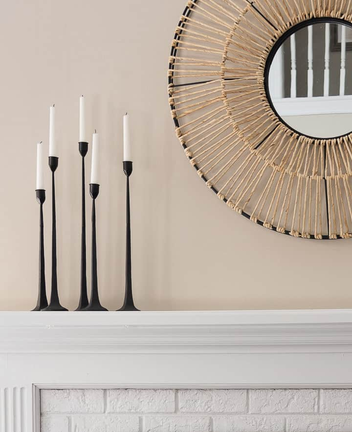 grouping of black candlesticks beside a white mirror on a white fireplace mantel