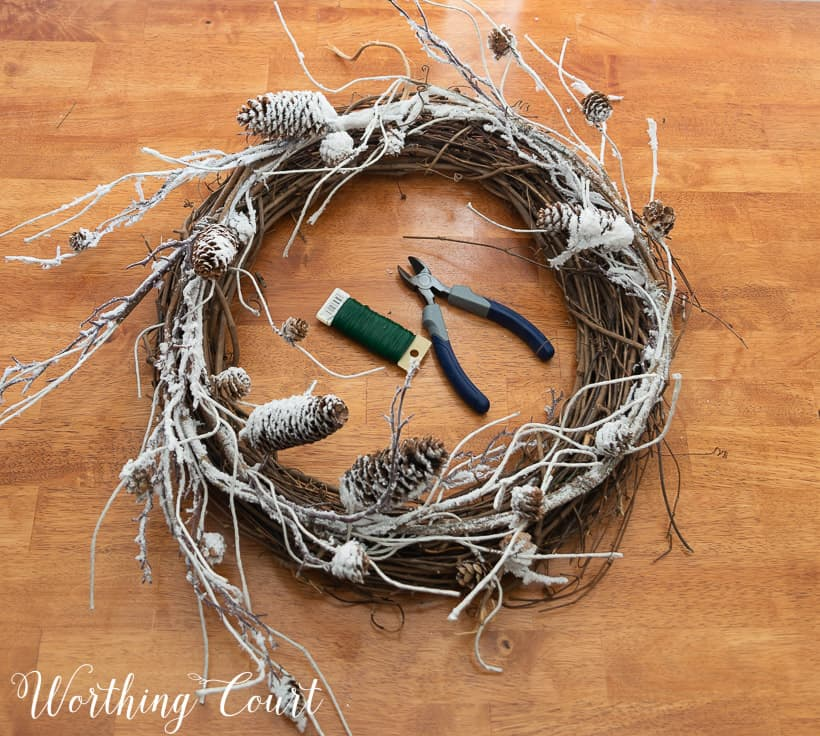 grapevine wreath, snowy garland, faux pine pieces and ribbon