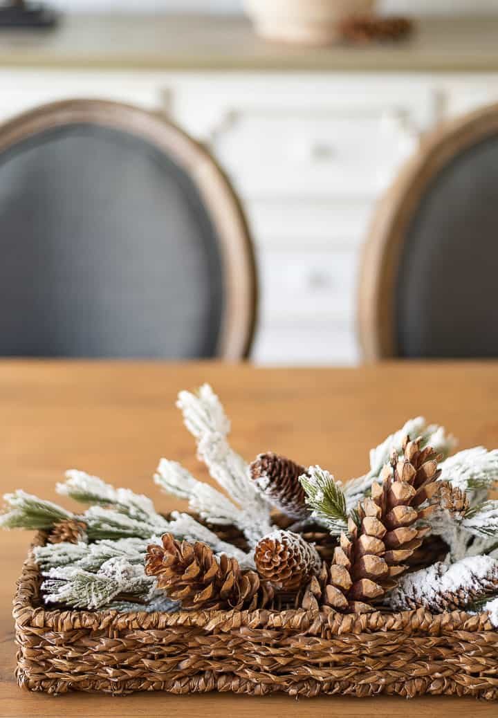 faux snow covered pine branches and pinecones in a small wicker basket on a dining table