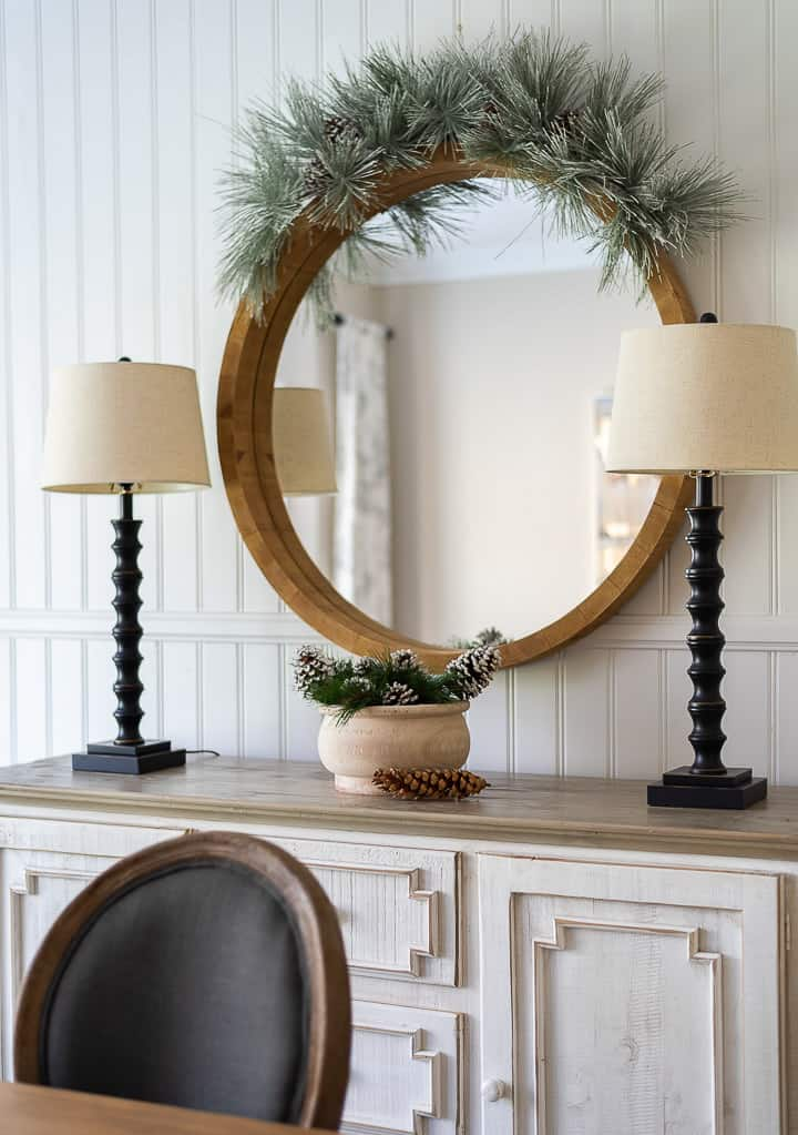 round mirror with greenery garland above over a white sideboard flanked by two lamps