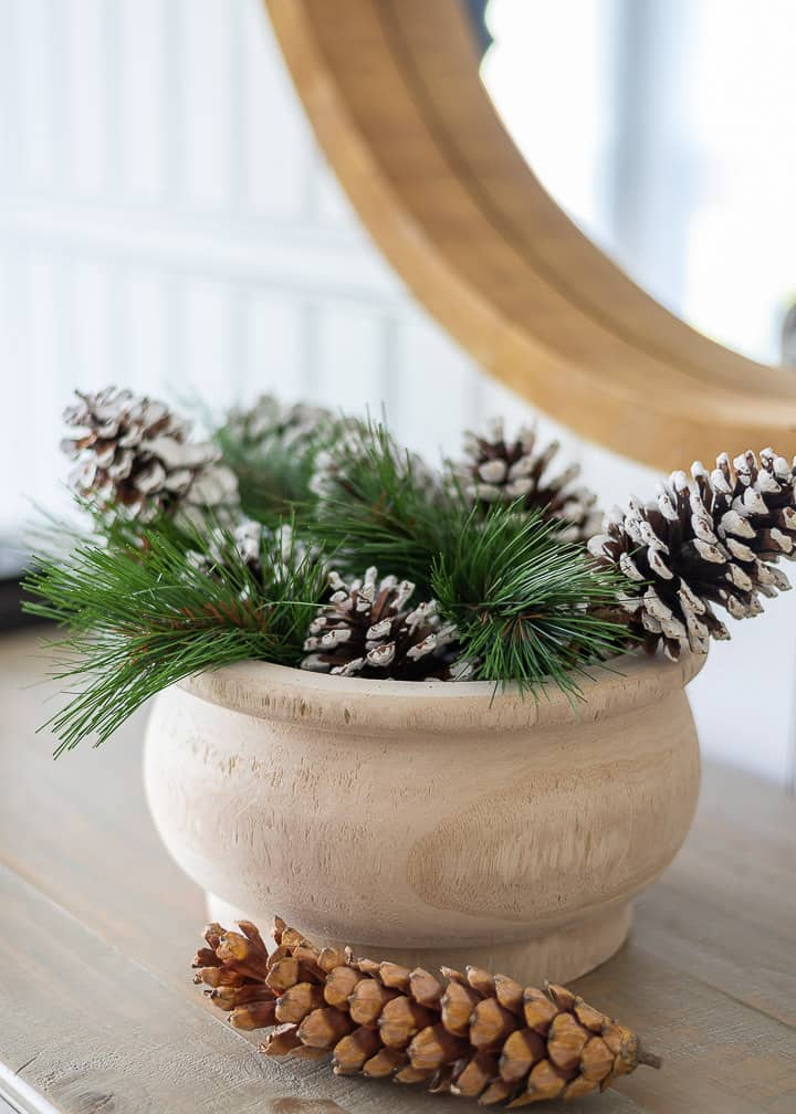 wooden bowl filled with evergreens and pinecones