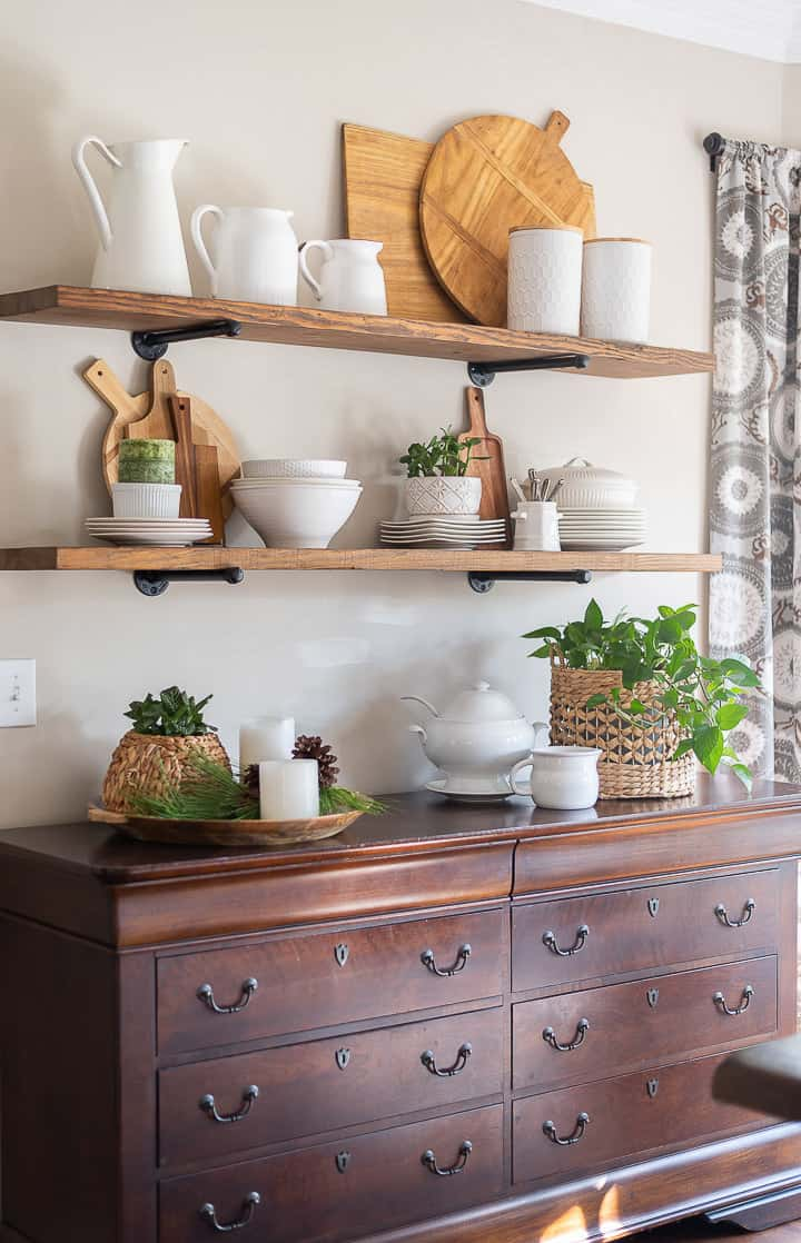 open shelves above wood sideboard decorated for winter with white dishes