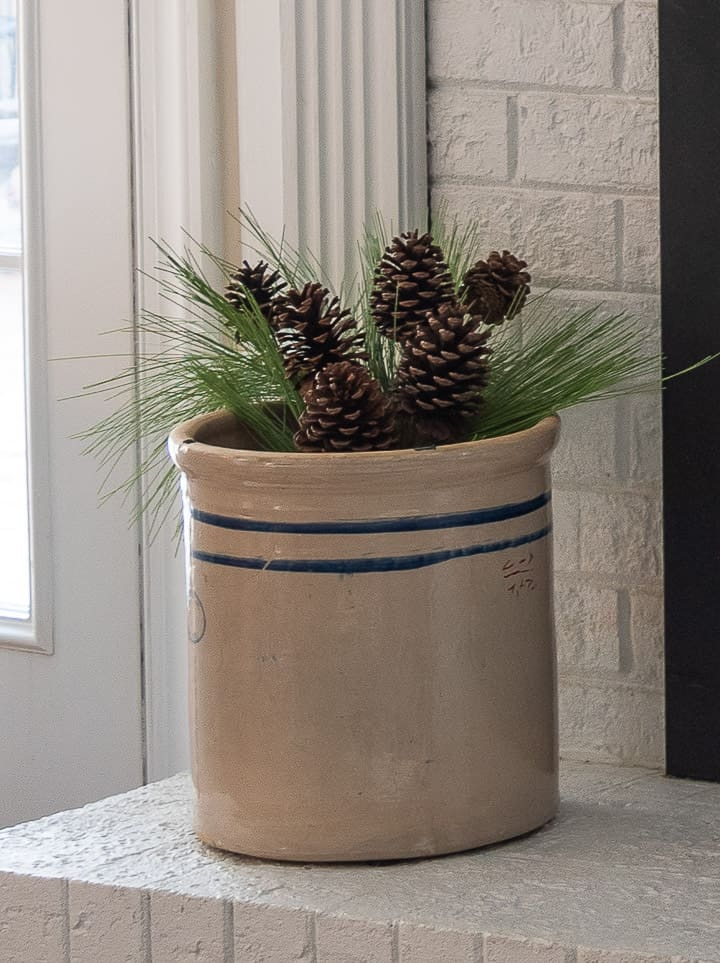 antique crock filled with faux pine greenery on a white fireplace hearth