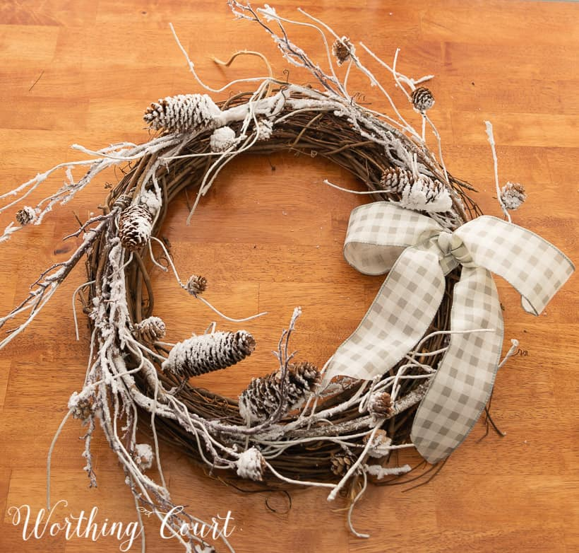 in process photo of the making of a wreath with snowy branches, pinecones and a bow