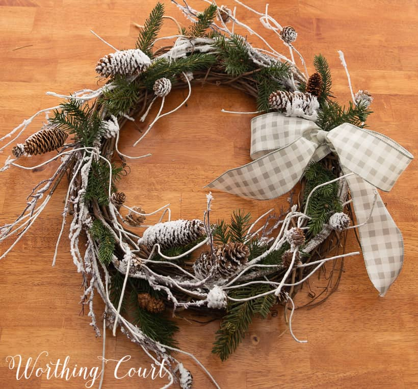 closeup of a winter wreath with snowy branches, pine branches and a bow