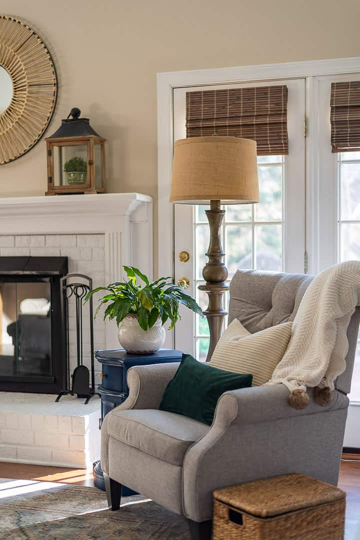 gray chair, floor lamp, blue side table sitting in front of windows and beside a white fireplace