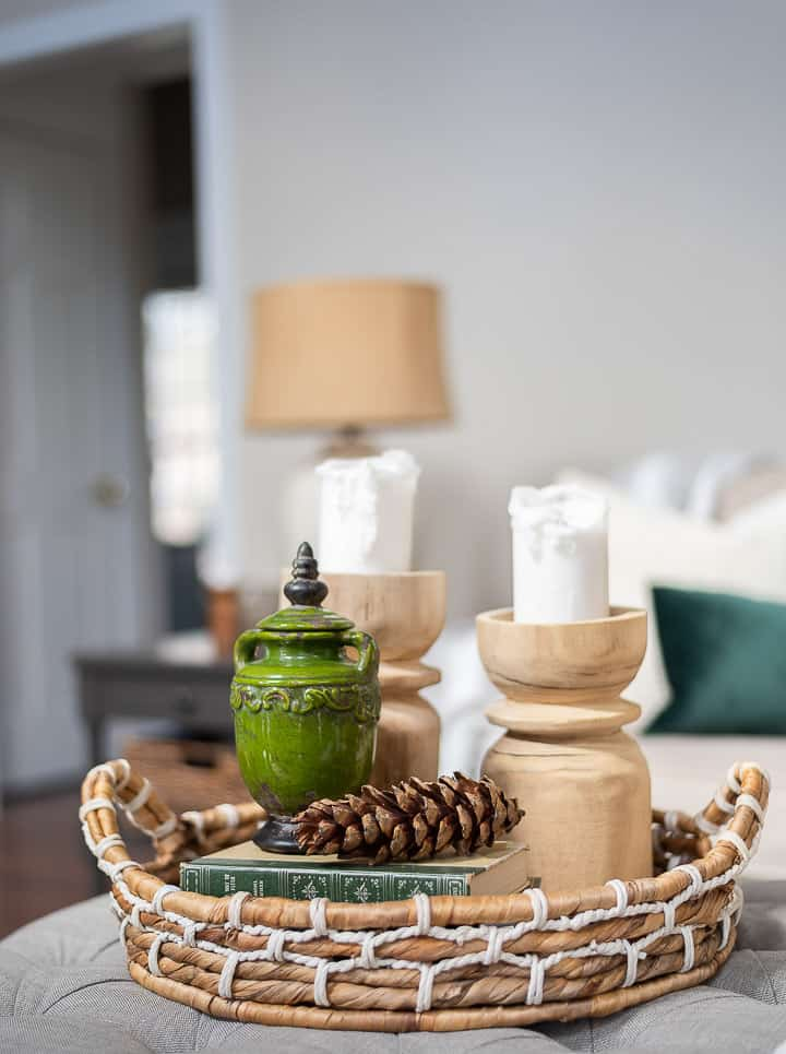 coffee table vignette in a round wicker tray basket with wood candlesticks, a green jar, a large pinecone and some stacked books