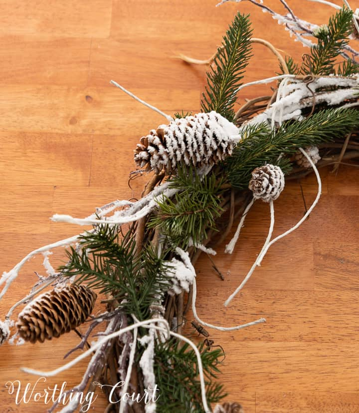 close up of snowy pinecones and pine branches on a grapevine wreath